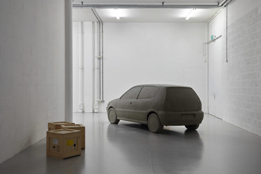 The bright white gallery has three wooden crates on the floor and a life-size plasticine car next to it.
