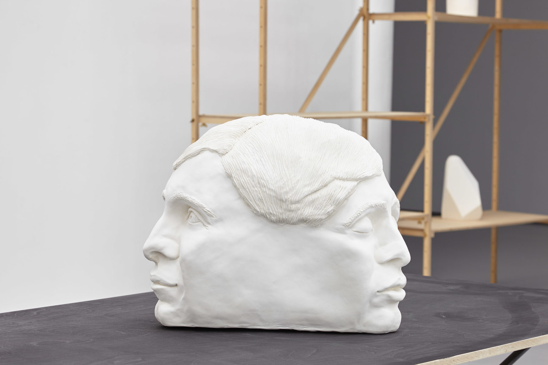 A large white sculpture of two heads joined together at the back is placed on a table in the gallery.