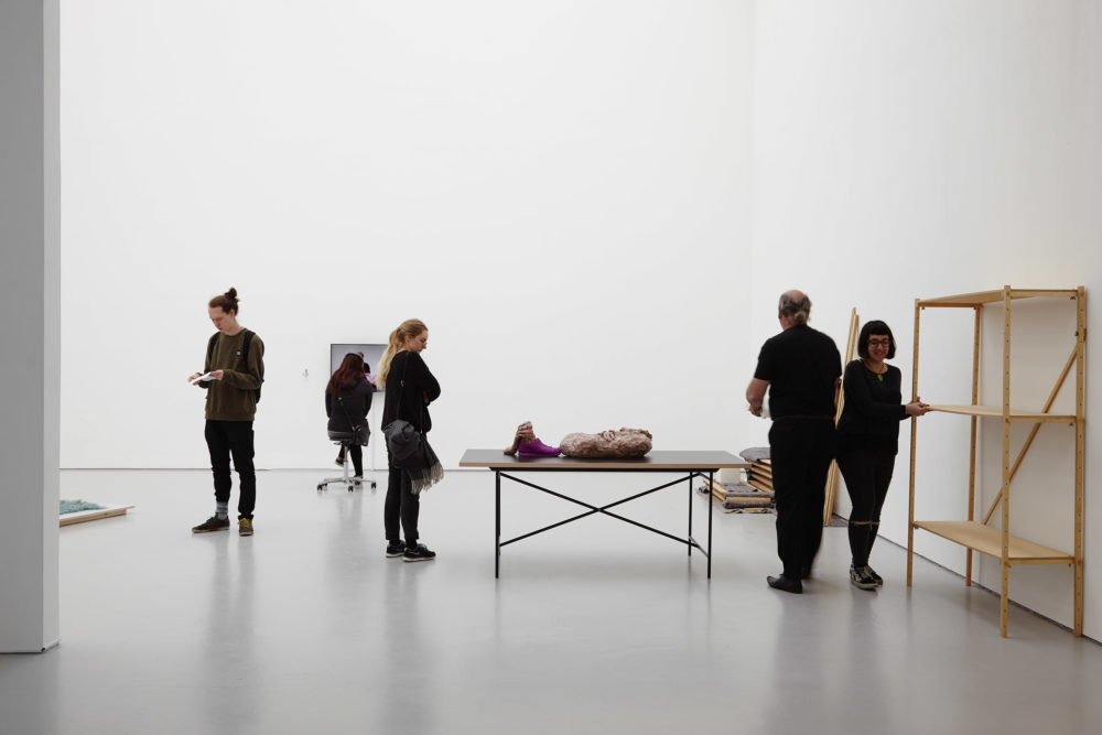 Visitors stand amongst the pieces. You can see an empty wooden shelving unit, a table with a pink clay mass on it, and on the far wall, a screen.