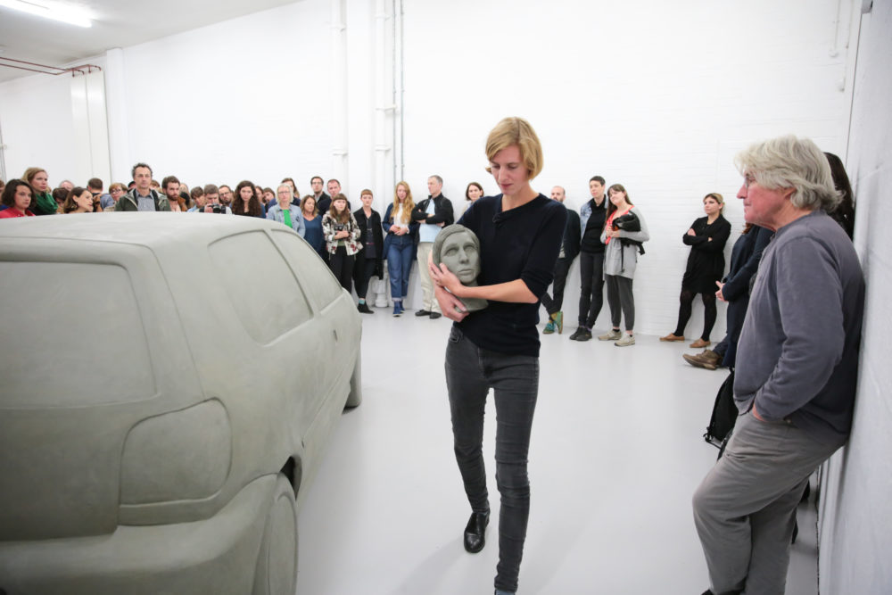 The artist holds a clay model of her own head her arms as she walks around a clay scale model of a car. This is a performance in a bright white gallery, a lot of people are standing in a large circle around her and the clay car, watching her.