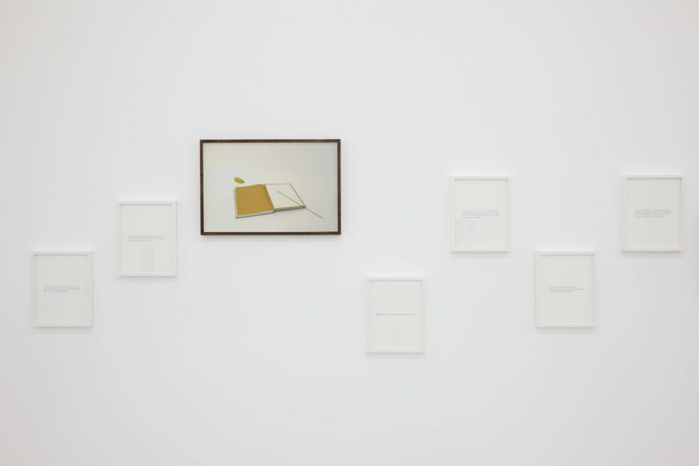 Six white frames hang on the gallery wall. One frame is black and has a photograph of a notebook in it.