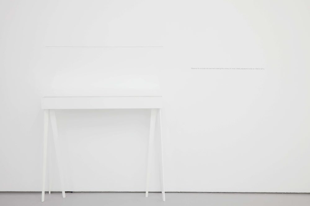 A white desk is placed in front of a white gallery wall so it is only just visible.