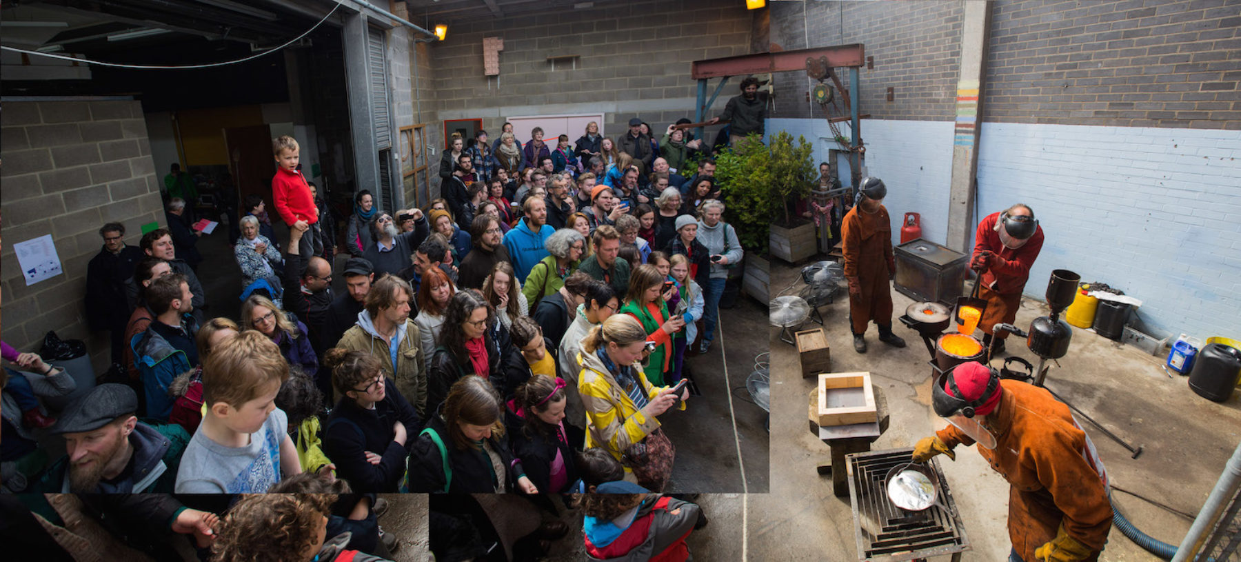 A large group of people are crowded in our sculpture yard watching three people, wearing protective clothing, pour molten metal into a cast.