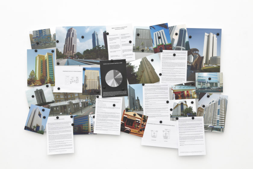Installation view of Wealth of Nations (2010). Lots of photographs of buildings are pinned to a corkboard, alongside graphs and cards that are heavily printed with text.