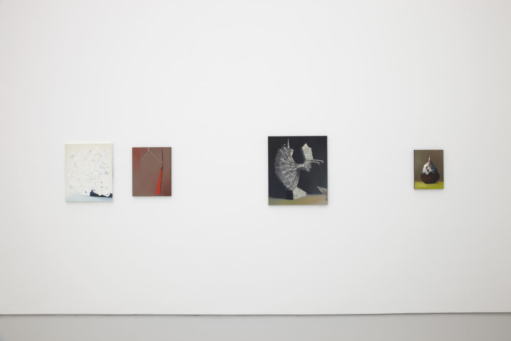 Installation shot: Four unframed paintings hang on a white wall.