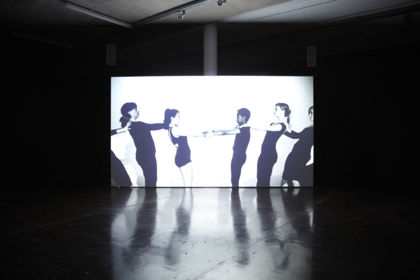 Installation view of Jesse Jones The Struggle Against Ourselves (2012). A projection of five people with their hands on one anothers' shoulders plays in a dimly lit gallery.