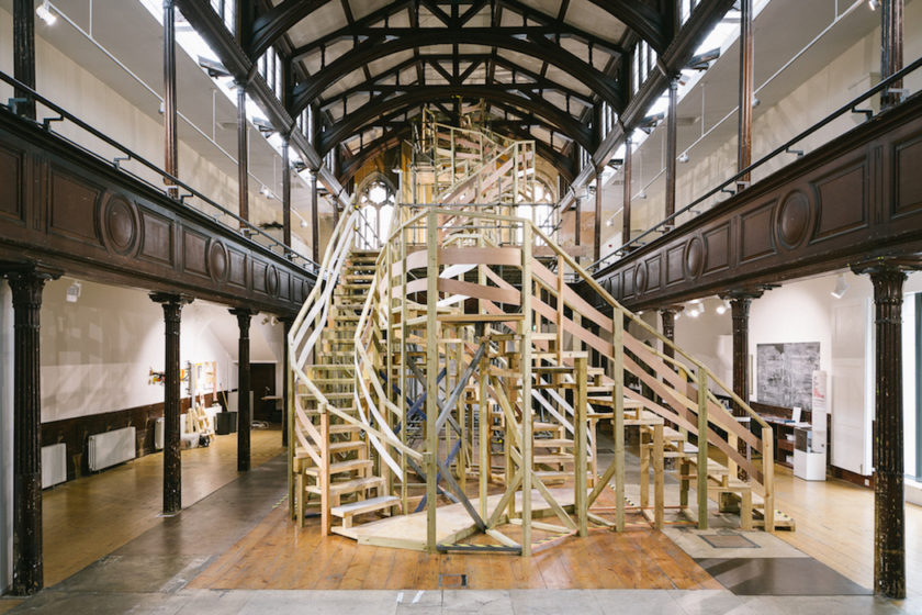 Installation: A maze of wooden stairs has been built in double-height room, with balconies running either side of where the first floor would be.