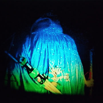 Film still: A person wearing a blue robe has their back to the camera, they also have a weapon on their back - they look like a fantasy character.