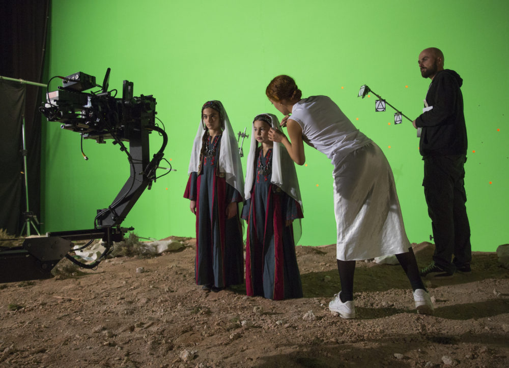 Production shot: Two young people are stood on sand in front of a green screen, they are wearing white headscarfs whilst the artist tends to their clothes. A member of the crew stands behind.