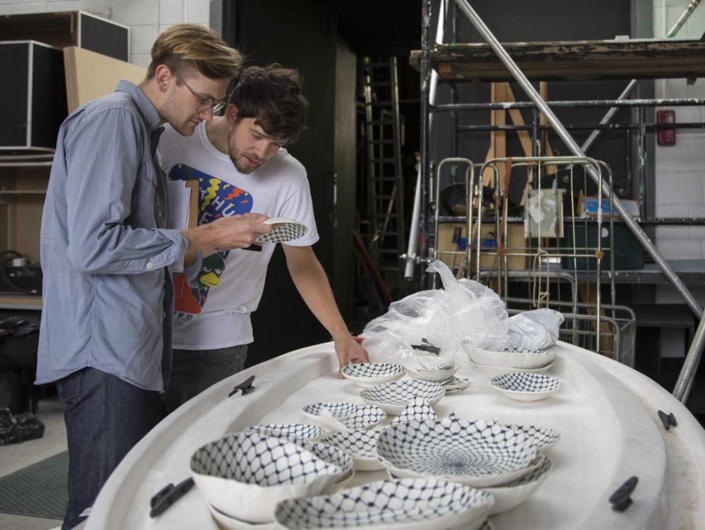 Production shot: Two men study porcelain bowls.