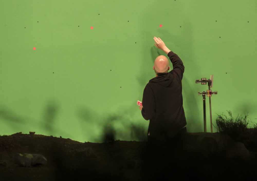 Production shot: A man tends to a green screen.