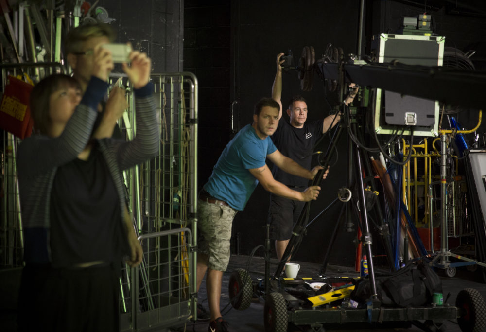 Production shot: Four crew members work on a film set.