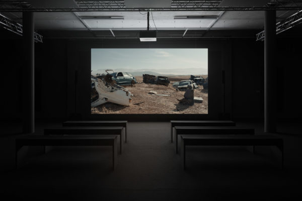 Installation view: A screen shows cars in a junkyard in a sandy environment.