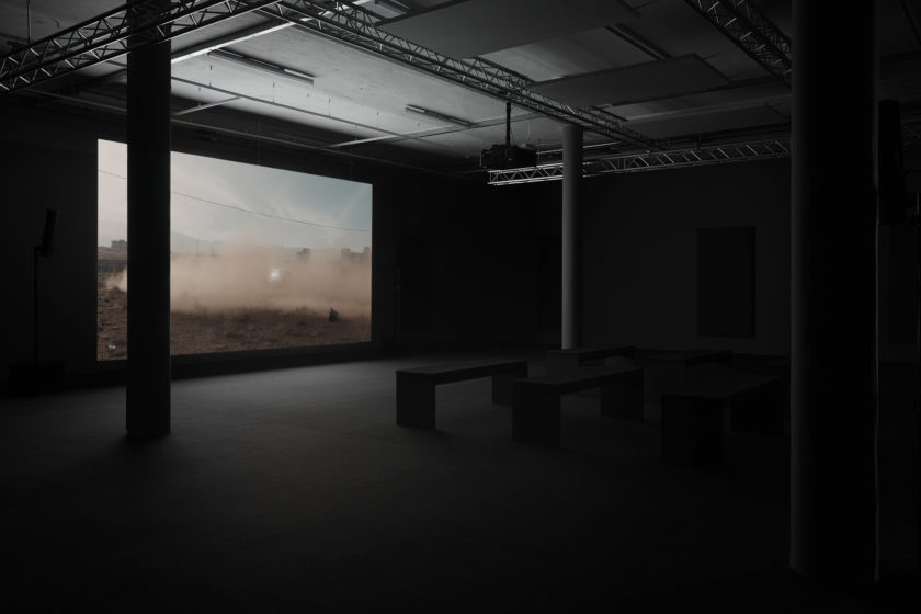 Installation view: A screen shows a car surrounded by dust it has made. In front of the screen are six benches.