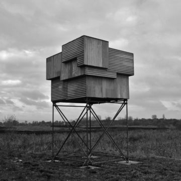 A structure made from a cube of scaffolding poles, topped with a shack of corrugated iron stands in a field.