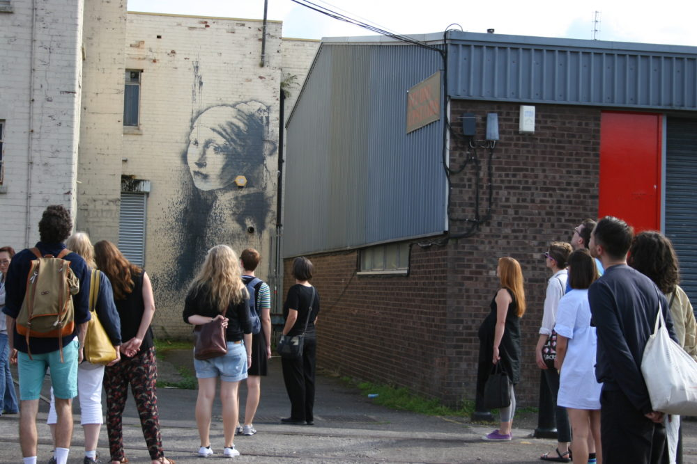 A group of people stand in a car park. A famous mural by Banksy, The Girl With the Pierced Eardrum, is on the wall behind them.
