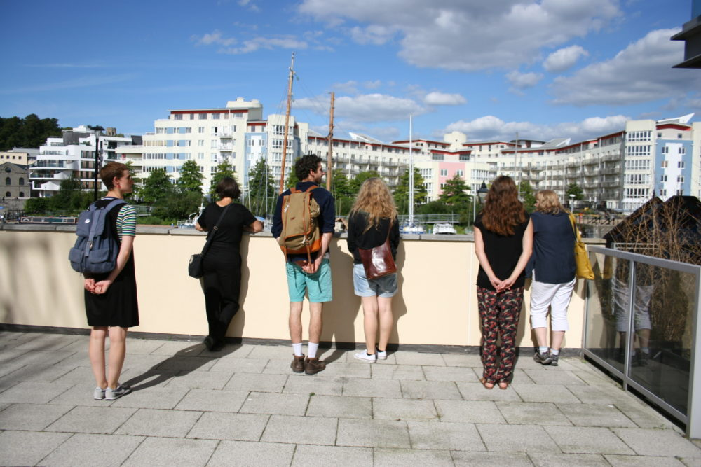 Six people look at Bristol's Harbour from a balcony. The sun is shining.