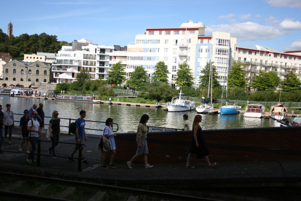 A group of people walk down Bristol Harbour on a sunny day.