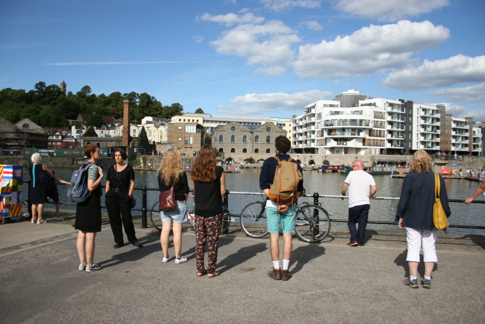 A group of people look out at Bristol Harbour on a sunny day.