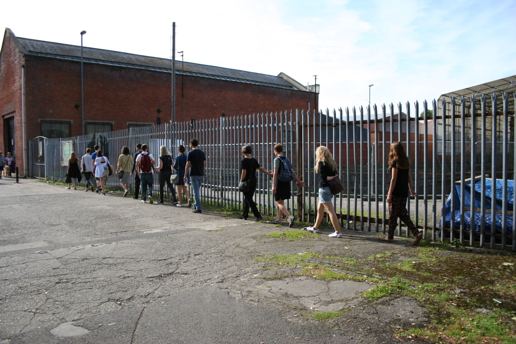 A group of people walk alongside an unfriendly metal fence.