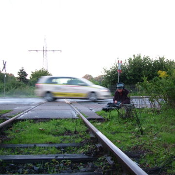 A photograph of a man using recording equipment next to a level crossing. A car crosses the level crossing in a blur.