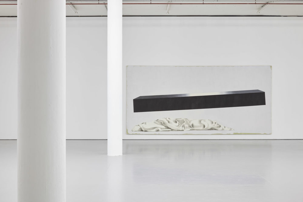 Installation shot: A painting of a shiny black long thin cuboid hovering above a pile of srunched up white fabric.