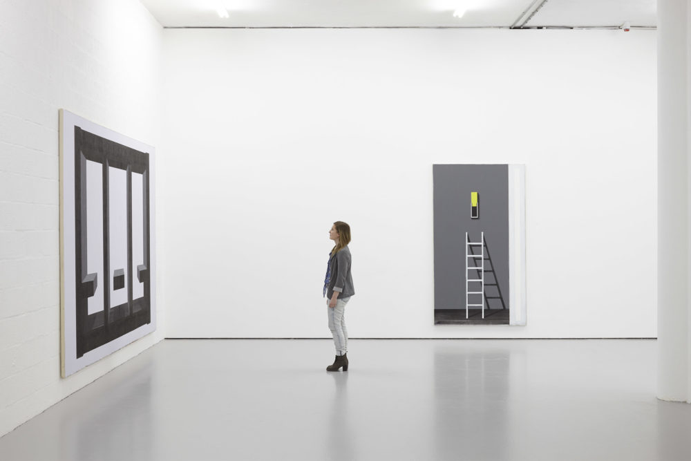 A visitor studies the paintings on the gallery wall.