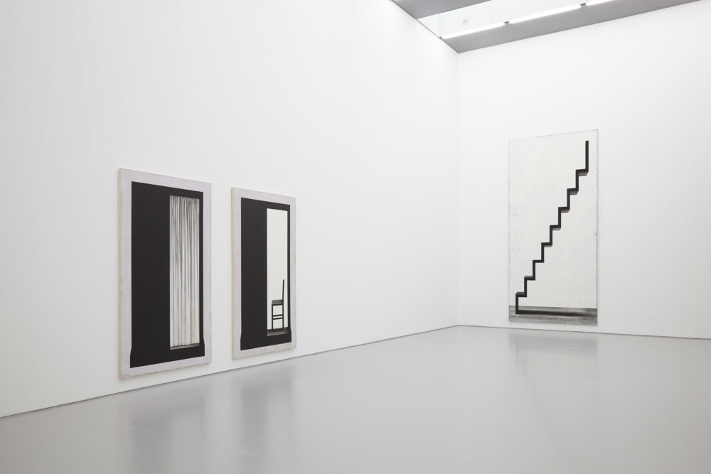 Installation shot: Three large black and white paintings hang in the gallery. Two are of a photo booth, and the other is of a staircase.