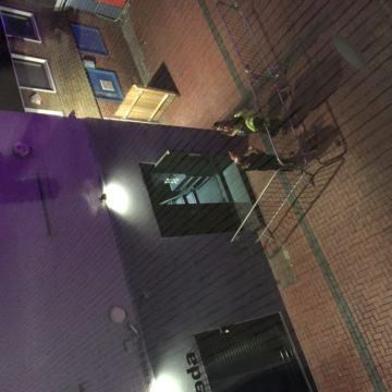 A photograph of what looks to be an entrance to an unpopular nightclub; only the bouncers stand outside. The image has been taken from high up in a nearby building and you have to turn your head to work it out.