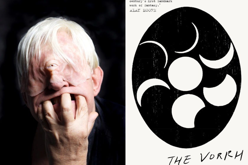 The author Brian Catling, dressed as a cyclops, next to their book The Vorrh.