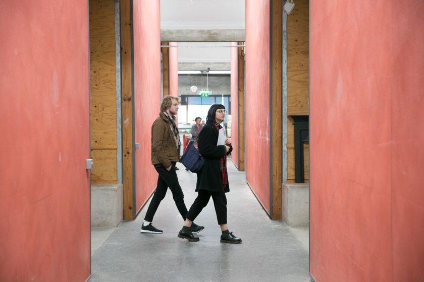 Two visitors walk between artist studios.