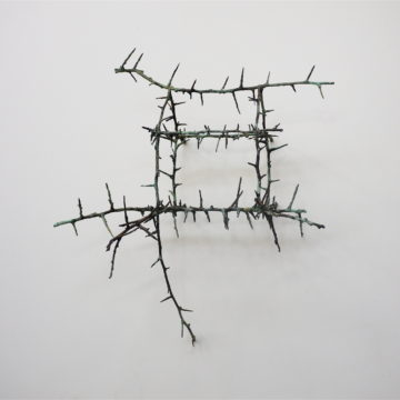 Sculpture: Some thorny twigs have been bound together to create the outline of a 3D house like structure.
