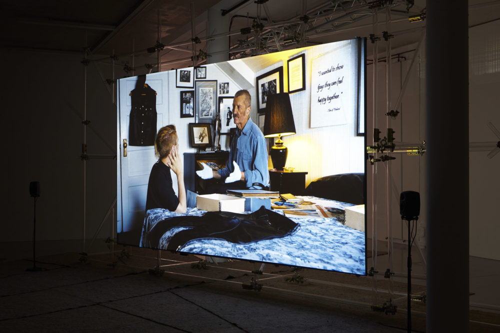 The screen shows a scene of two men sat in deep discussion in a bedroom. A pair of leather trousers are laid on the bed, as are lots of boxes.