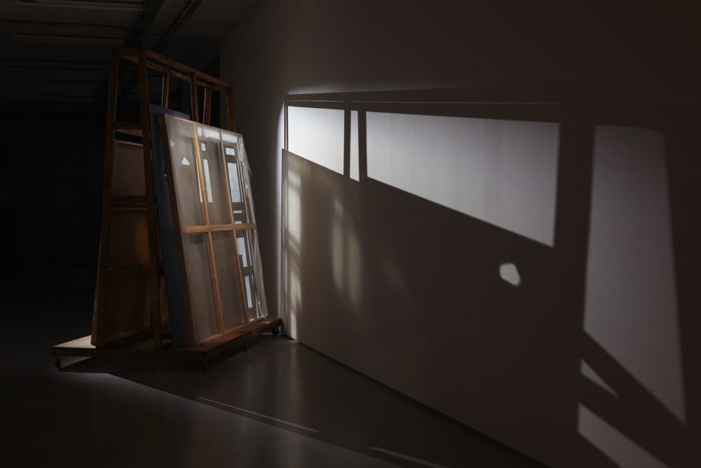 A large wooden structure with building materials stacked on it casts a dramatic shadow in the gallery.
