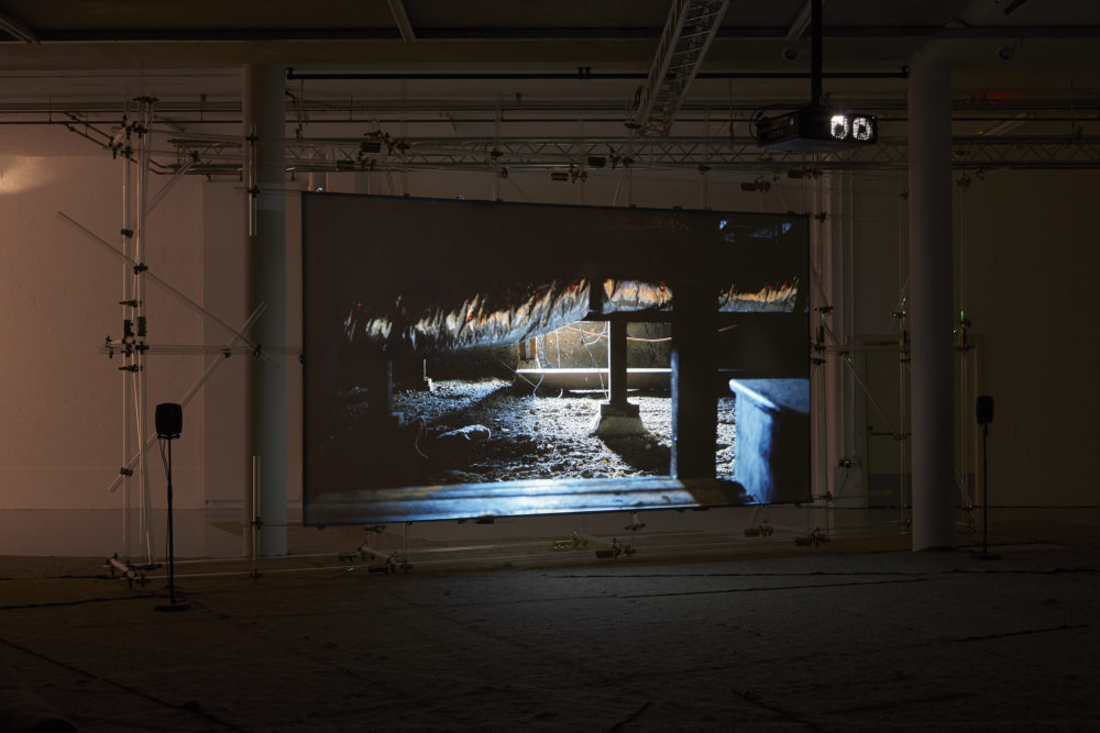 The scaffolding supported screen shows a scene of a basement beneath a working building - a thick layer of dust lies on the floor and a large ceiling pipe is covered in foil.