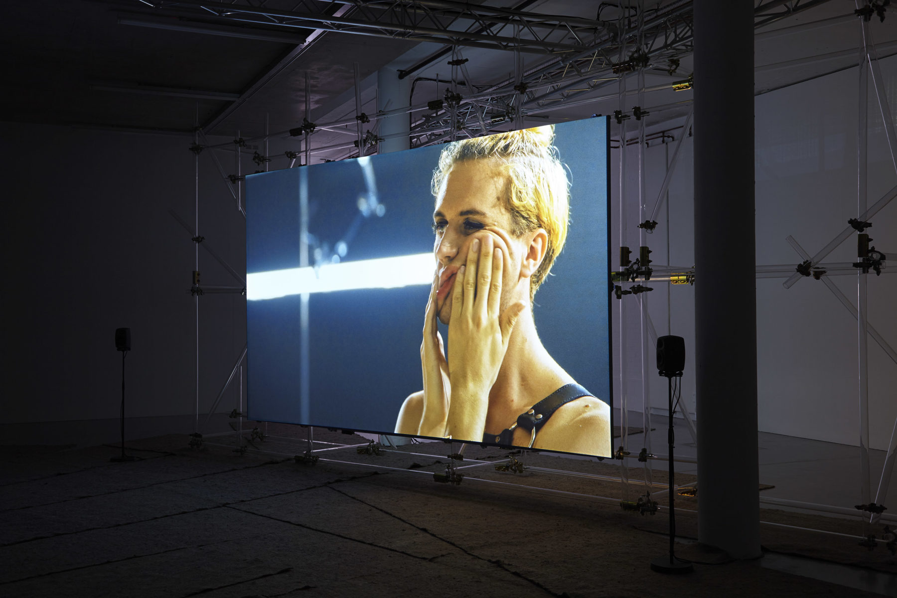 A screen has been erected at Spike Island gallery using a lot of scaffolding. On the screen, a blonde person is wearing leather bondage gear and kneading their face.