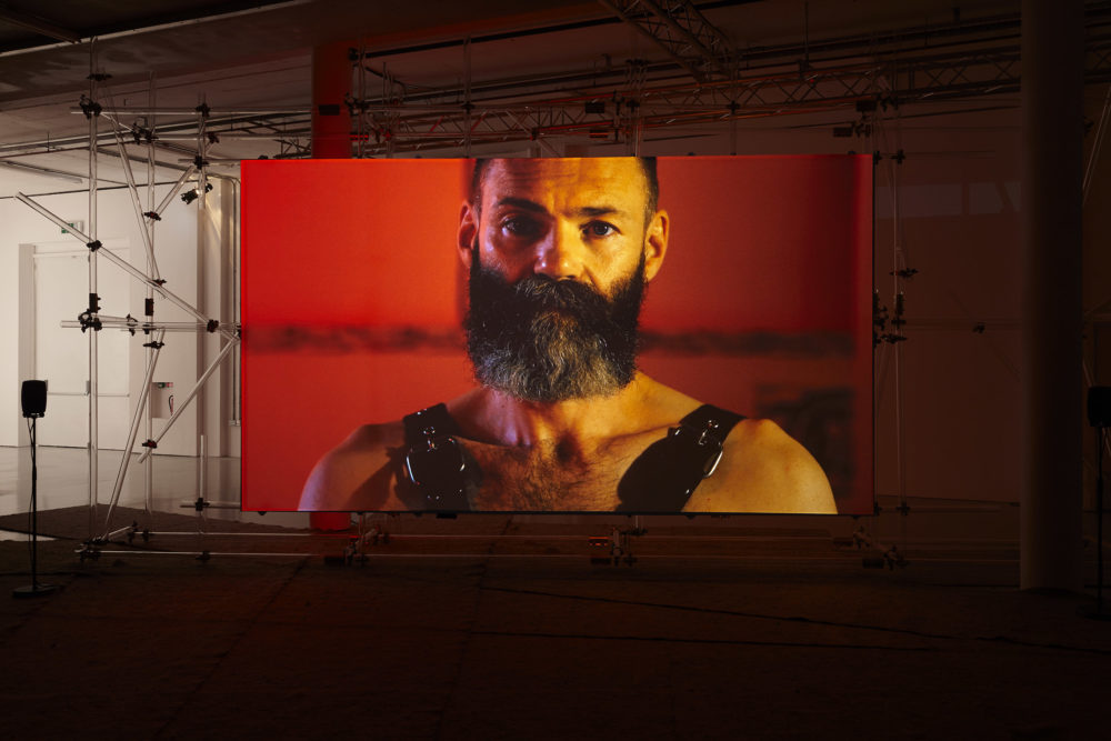 A screen has been erected at Spike Island gallery using a lot of scaffolding. On the screen, a person with a full dark beard is wearing leather bondage straps and looking directly at the camera.