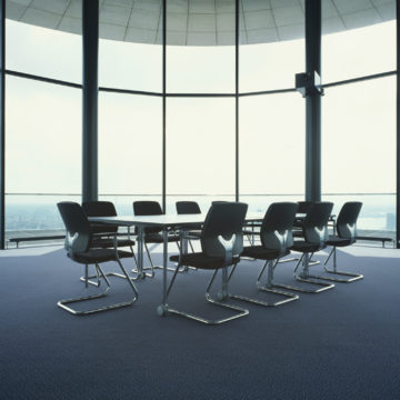 A table set up for board meetings sits in an otherwise empty room with walls made of glass. It seems this room is the tallest for miles.
