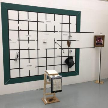 Installation: A grid is painted on a wall, various objects hang from the grid. A plinth is placed in front of the grid with a book on top of it. To the right of the grid is a free-standing framed picture.