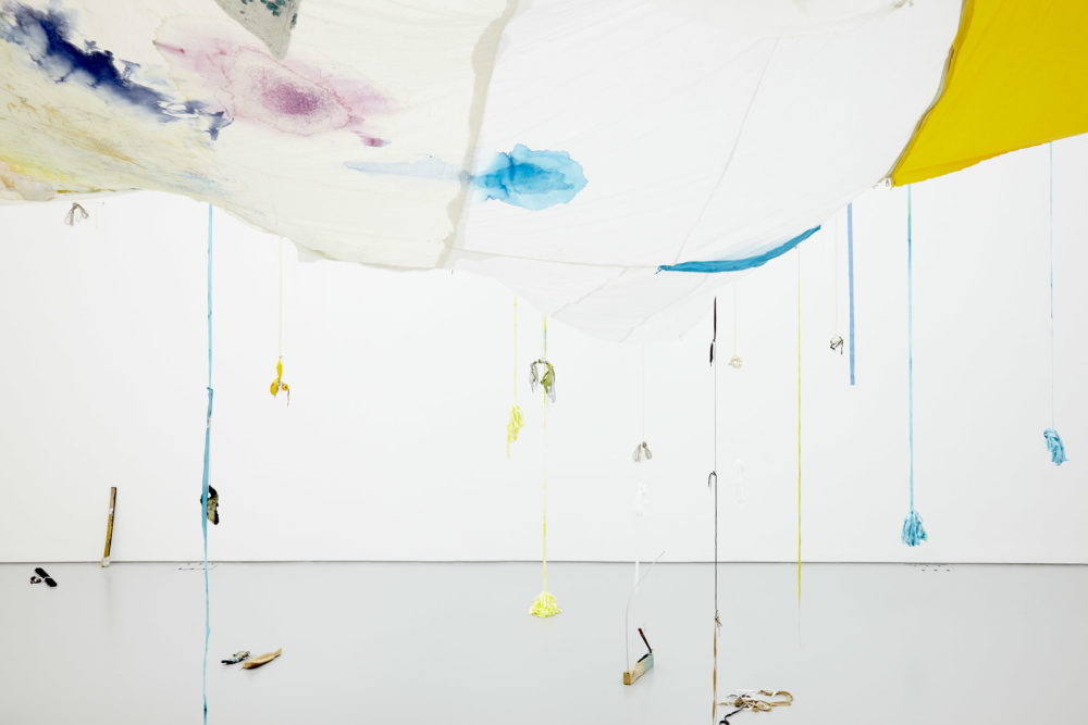Large swathes of fabric hang down from the gallery ceiling. A white piece of fabric has been discolored in patches with pink and blue inks. Ribbons hang from these fabric swathes, some have weights which appear to be abstract shapes made from ceramic.