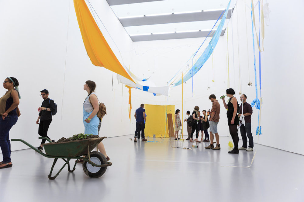 Visitors study the art in the gallery - in the foreground a wheelbarrow full of mud or clay. In the background a swathe of sunny yellow fabric is hung on a wall. The ceiling has more fabric hanging from it - this time in yellow, blue and white.