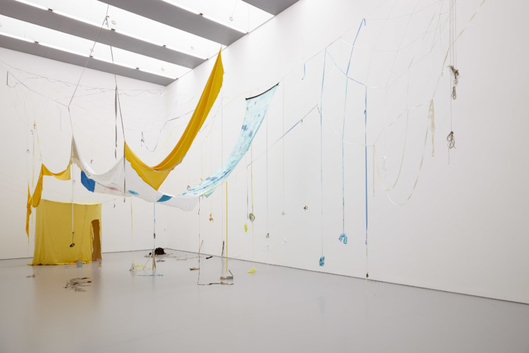 Photograph of a large white gallery space with large windows across the ceiling. A yellow tent-like structure is hanging in the distance, and swathes of fabric hang down from the ceiling in yellow and blues. Ribbons dangle from the fabric strips, and some have small clay objects tied to them.