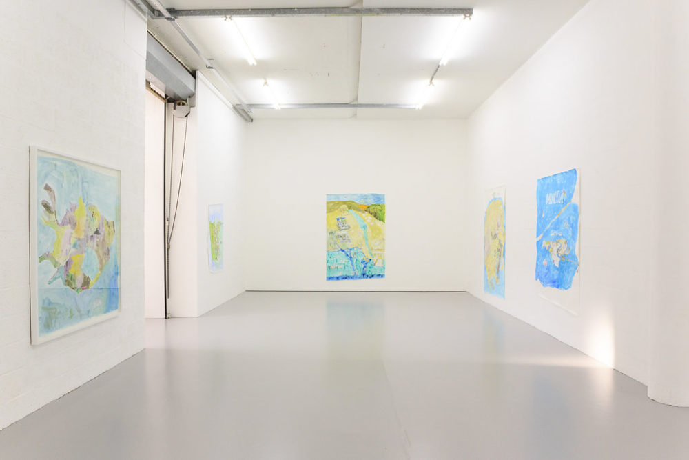 The white walls of the gallery are decorated with large pictures of maps in bright blue and green and yellow.