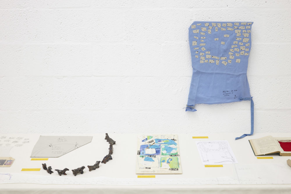 A white table in a white gallery has various ephemera laid out neatly and labelled.