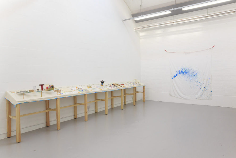 Various ephemeral pieces sit on a table in the white gallery. On another wall a piece of white fabric is hung up with paint sprayed on it.