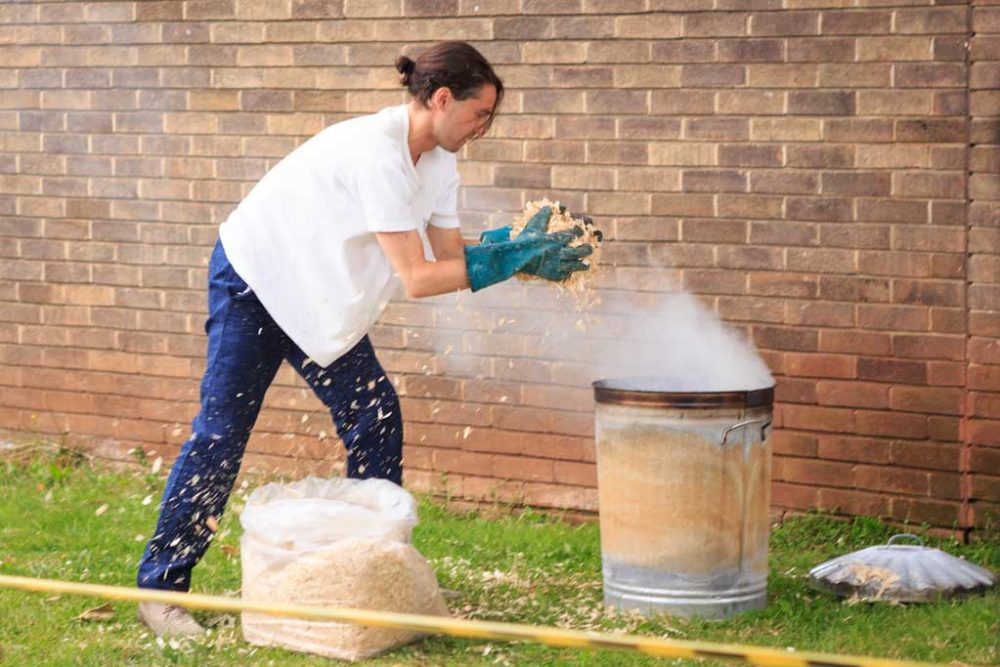 The artist is putting sawdust into a burning metal dustbin in order to make a rudimentary kiln. This is happening outside of the Spike Island building - some yellow and black tape prevents visitors from getting too close.