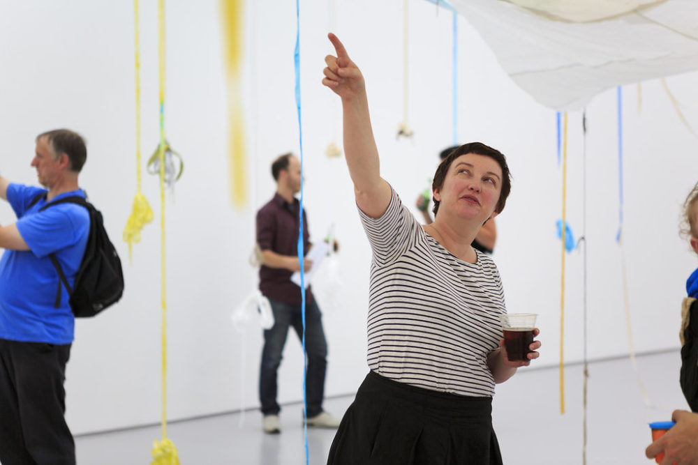 A visitor wearing a striped shirt points upwards. Around her, ribbons of blue, yellow and white hang down from the ceiling.
