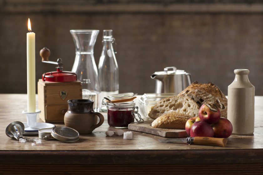 A table scene - a coffee grinder, a pot of jam, a loaf of bread, some apples all sit on a table.
