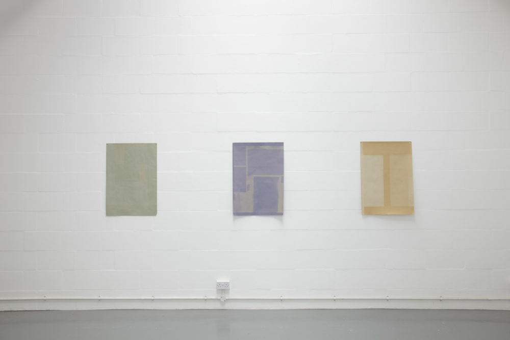 Installation view of Sara MacKillop, Faded Paper (2011). Three sheets of sugar paper, faded by the sun, are pinned to the white gallery wall.