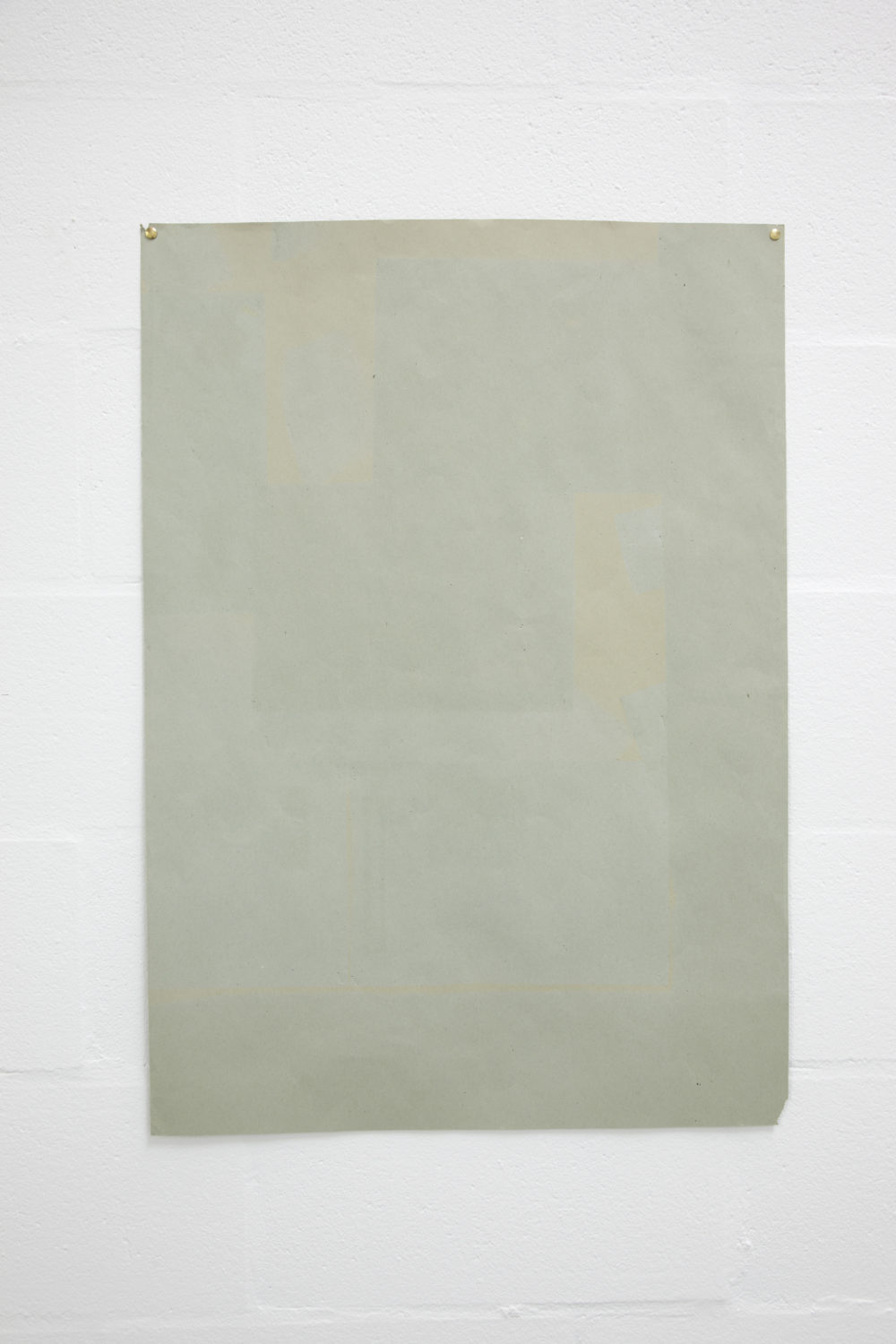 Installation view of Sara MacKillop, Faded Paper (2011). A sheet of green sugar paper, faded by the sun, is pinned to the white gallery wall.